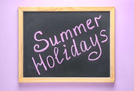 Chalkboard with phrase SUMMER HOLIDAYS on lilac background, top view. School's out