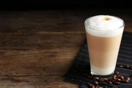 Delicious latte macchiato and coffee beans on wooden table. Space for text