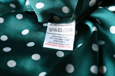 Clothing label with care instructions and content information on green polka dot garment, closeup Stockfoto