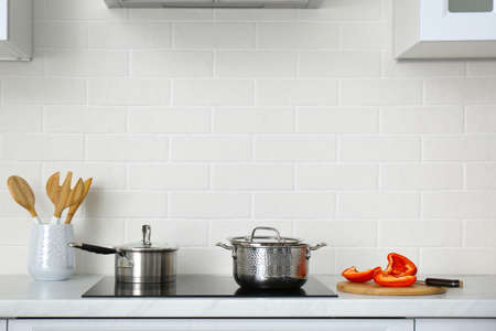 Kitchen counter with utensils and cookware on stove
