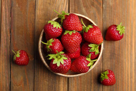 Delicious ripe strawberries in bowl on wooden table, flat lay