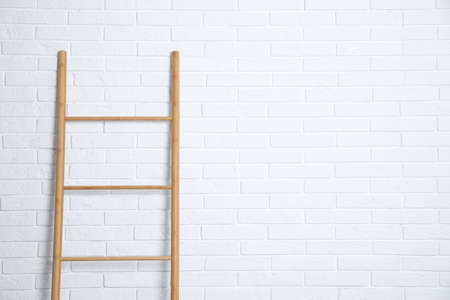 Modern wooden ladder near white brick wall. Space for text