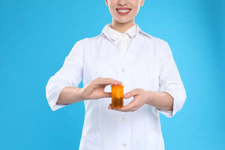 Professional pharmacist with pills on light blue background, closeup Stock Photo