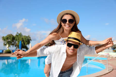 Happy couple near swimming pool. Summer vacation
