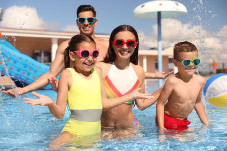 Happy family having fun at water park. Summer vacation