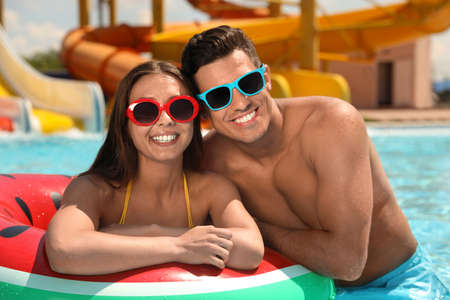 Happy couple with inflatable ring at water park. Summer vacation