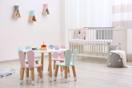 Cute baby room interior with cot and little table Standard-Bild