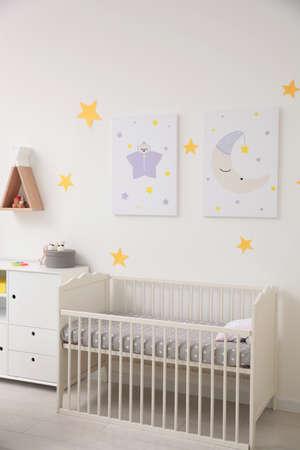 Stylish baby room interior with crib and decor elements Stockfoto