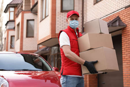 Courier in protective mask and gloves with boxes near car outdoors. Delivery service during coronavirus quarantine