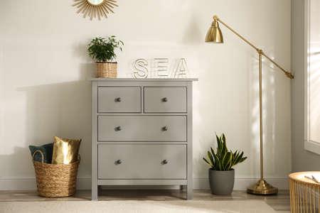 Gray chest of drawers in stylish room interior Archivio Fotografico