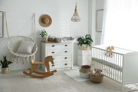 Chest of drawers with changing tray and pad near comfortable cradle in baby room. Interior design
