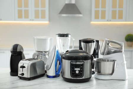 Set of modern home appliances on white marble table in kitchen Foto de archivo