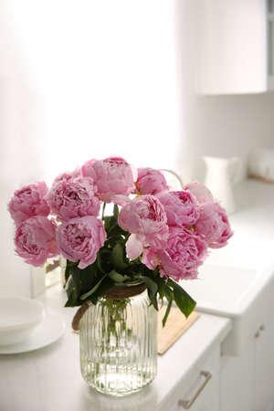 Vase with bouquet of beautiful pink peonies in kitchen Stock fotó