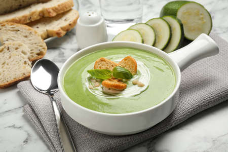 Tasty homemade zucchini cream soup served on marble table