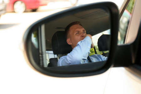 Tired young man yawning in his auto, view through car side mirror