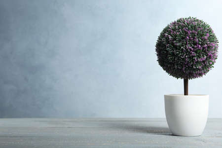 Artificial plant in flower pot on light gray wooden table. Space for text