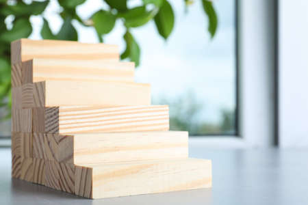 Steps made with wooden blocks on light gray table indoors, space for text. Career ladder