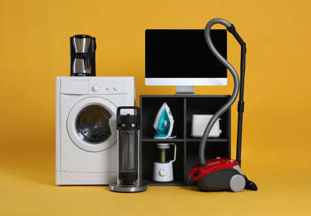 Set of different home appliances with vacuum cleaner on yellow background