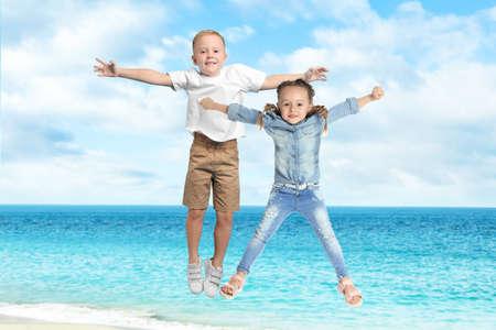 Cute school boy and girl jumping on beach near sea. Summer holidays