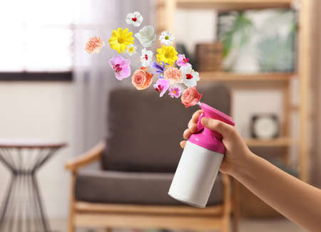 Woman spraying air freshener at home, closeup. Flowered aroma