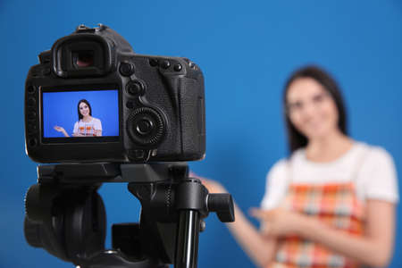Young blogger recording video against blue background, focus on camera screen