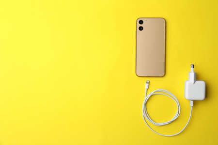 Smartphone and USB charger on yellow background, flat lay. Space for text