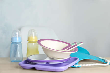 Set of plastic dishware on wooden table indoors. Serving baby food