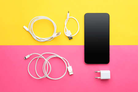 USB charge cables, power adapter and smartphone on color background, flat lay. Modern technology Zdjęcie Seryjne