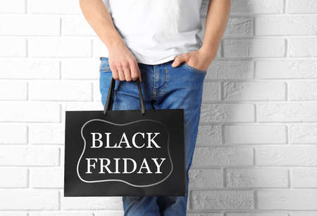Man holding shopping bag with text BLACK FRIDAY against brick wall, closeup Stock fotó - 154673874