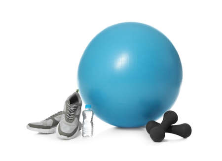 Fitness ball, sneakers, bottle of water and dumbbells isolated on white