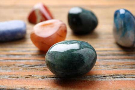 Beautiful gemstones on wooden table, closeup. Healing crystals