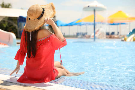 Young woman sitting near outdoor swimming pool. Space for text