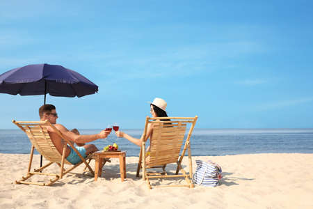 Happy couple with wine on sunny beach at resort