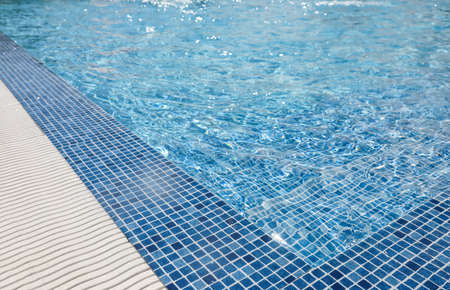 Outdoor swimming pool with clear water on sunny day. Summer vacation