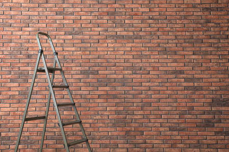 Metal stepladder near brick wall. Space for text