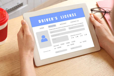 Woman filling in driver's license form online on website using tablet, closeup