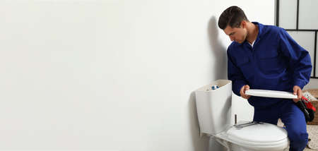 Professional plumber working with toilet bowl in bathroom, space for text. Banner design