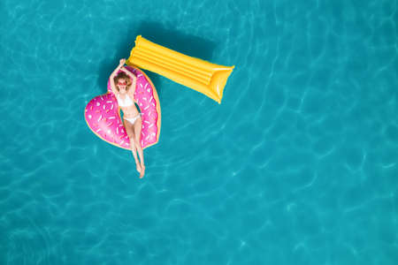 Happy woman with inflatable mattress and ring in swimming pool, top view. Summer vacation