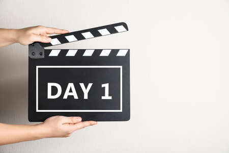 Starting new life chapter. Woman holding clapperboard with text Day 1, closeup