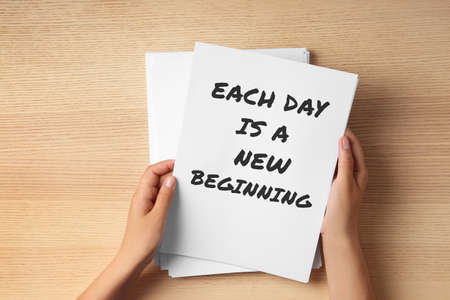 Woman holding paper with inspirational text Each Day Is A New Beginning at wooden table, top view. Change your life
