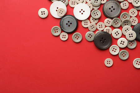Many colorful sewing buttons on red background, flat lay. Space for text