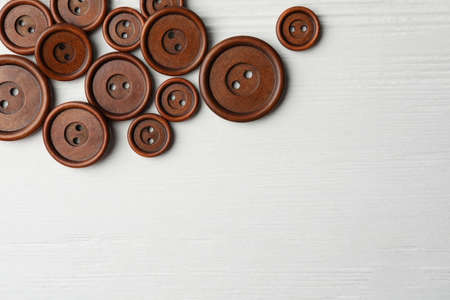 Many brown sewing buttons on white wooden background, flat lay. Space for text
