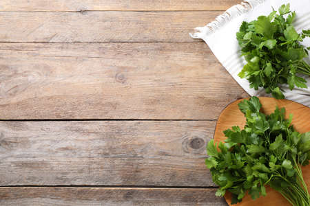 Bunch of fresh green parsley on wooden table, flat lay. Space for text