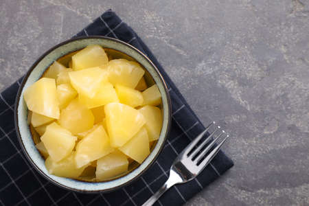 Tasty canned pineapple in bowl on gray table, flat lay. Space for text