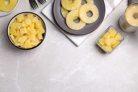 Flat lay composition with canned pineapple on light gray marble table. Space for text Zdjęcie Seryjne