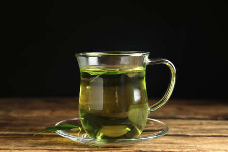 Cup of aromatic green tea on wooden table Imagens