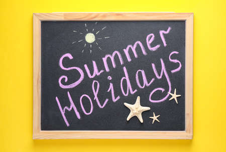 Chalkboard with phrase SUMMER HOLIDAYS on yellow background, top view. School's out