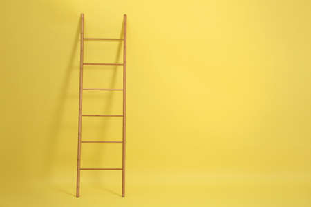 Modern wooden ladder on yellow background. Space for text