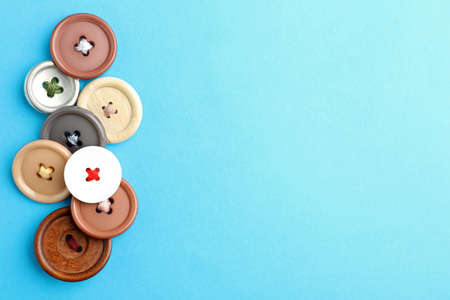 Many colorful sewing buttons on light blue background, flat lay. Space for text