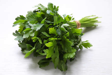 Bunch of fresh green parsley on white wooden table, closeup Imagens